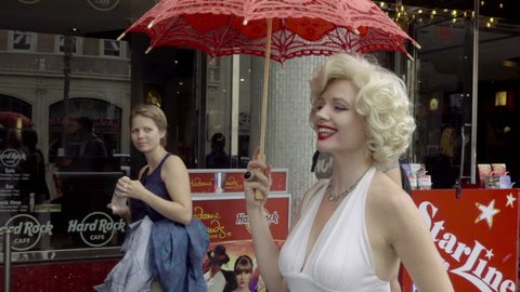 LOS ANGELES - NOV 1, 2016: Marilyn Monroe Impersonator Smiling At Baby And Waving At Tourists On Hollywood Boulevard In LA California. Tourists enjoy performances and impersonations of famous icons.