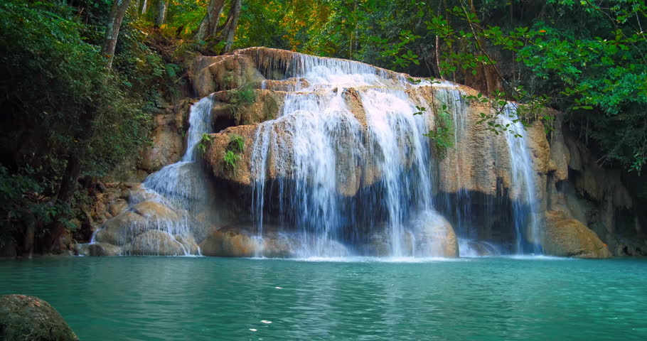 Serene and remote Erawan waterfall in tropical rain forest flows in emerald pond