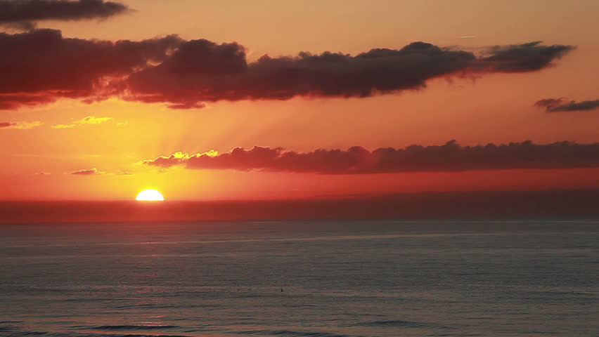 Sun is just beginning to rise above the ocean and clouds on the horizon of this beautiful sunrise view of sea and sky viewed from the 5th floor of a ocean front beach resort
