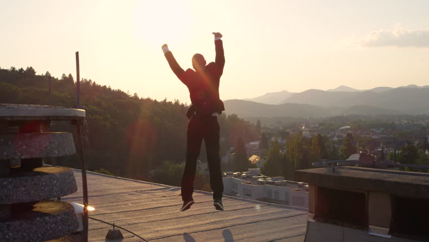 SLOW MOTION CLOSE UP DOF: Excited entrepreneur jumping for joy raising hands when successfully closing big business deal. Happy man rejoicing and leaping on the rooftop at amazing golden light sunrise