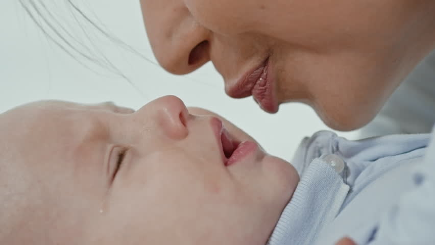 Close up of face of little baby crying as his mother kissing him and trying to sooth him   Shutterstock HD Video #22380133