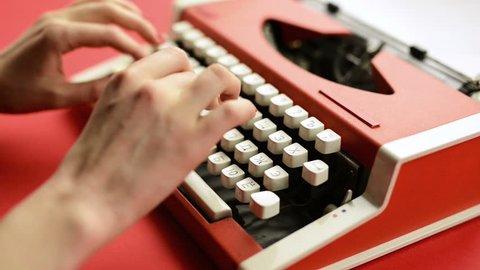 Closeup of woman hand typing on red vintage typewriter