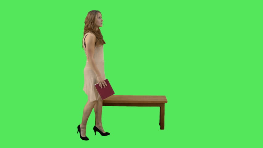 Female sitting on bench reading on green screen