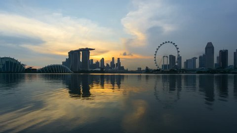 Beautiful Time lapse of Day to Night of Singapore skyline with reflection. 4K UHD. Zoom In Camera Motion.