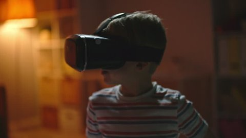 Little boy in virtual reality headset standing in dark room and looking around in amazement, ten trying to touch something invisible