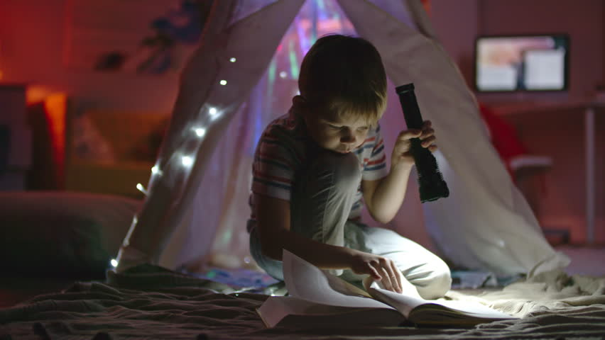 Little boy with flashlight sitting in his room near teepee decorated with fairy lights and looking at book