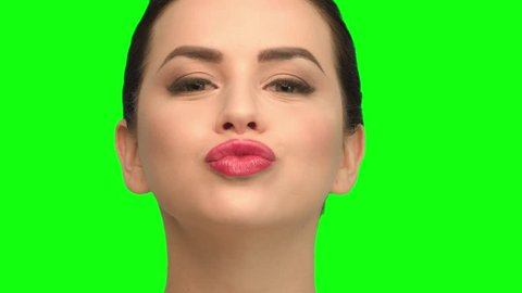 The girl winks and sends an air kiss, brunette on the green screen
