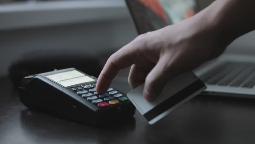 Man uses credit card terminal in the office. Close up shot. Concept of small business