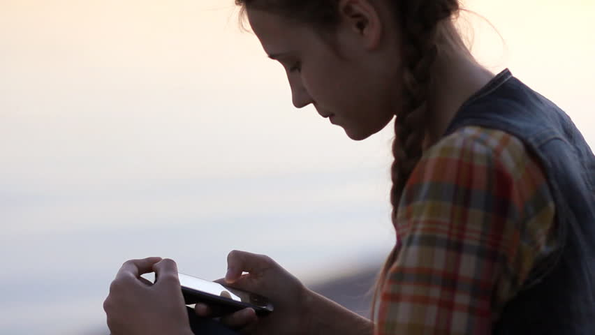 Young girl sms texting using app on smartphone outdoor. Side view silhouette of teenage girl with braids wearing plaid shirt and denim vest sitting by the lake at evening. | Shutterstock HD Video #22443103