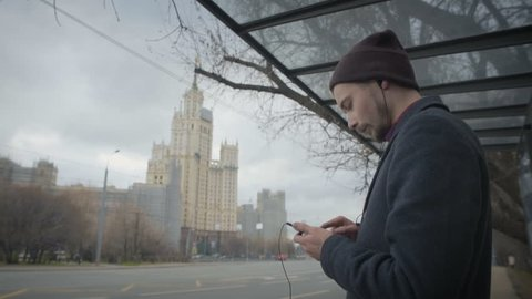 young man is staying alone on bus stop waiting for bus in moscow listening to music from his mobile dressed in black coat and dark hat during autumn cold day