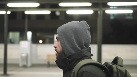MIllenial youth in hoodie at the train station at night, slomo 100p.A hooded young man is waiting for the train or walking along the platform with or witout his hoodie on, at night.