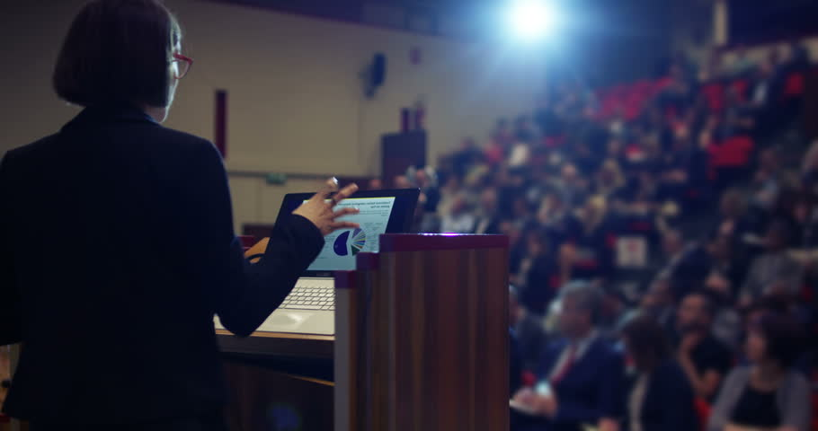 A woman holds a speech to the audience in an auditorium on a convention of economics and finance their business.concept:world economy,futuristic conference, holograms,technology,businessman conference