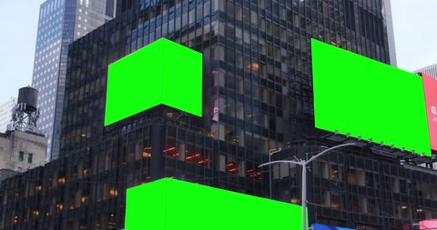 Green screen digital billboards on the side of a tall building in a large city.