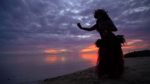 Young Polynesian female Tahitian hula dancer performing at sunset on ocean beach barefoot in traditional costume Tahiti French Polynesia South Pacific