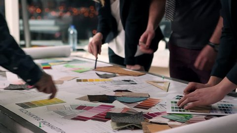 A group of young designers led by the head are working on the project of design business center, private home, studio, shop, office/Designers at Work