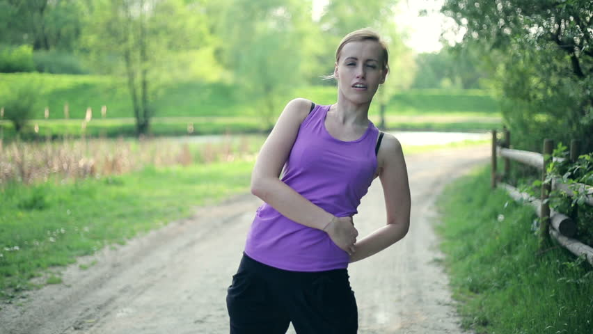 Young woman feeling pain in back during exercise, outdoors
