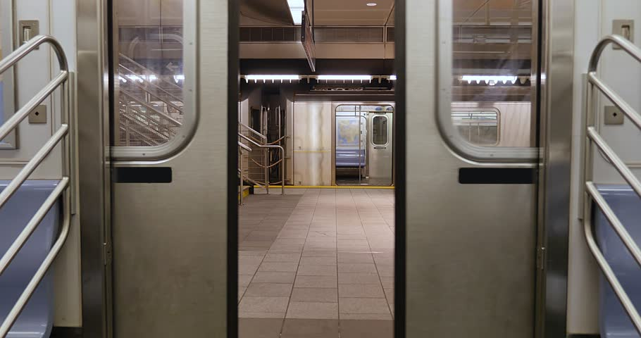An interior view of the doors on a New York City subway car as they open at the platform.
