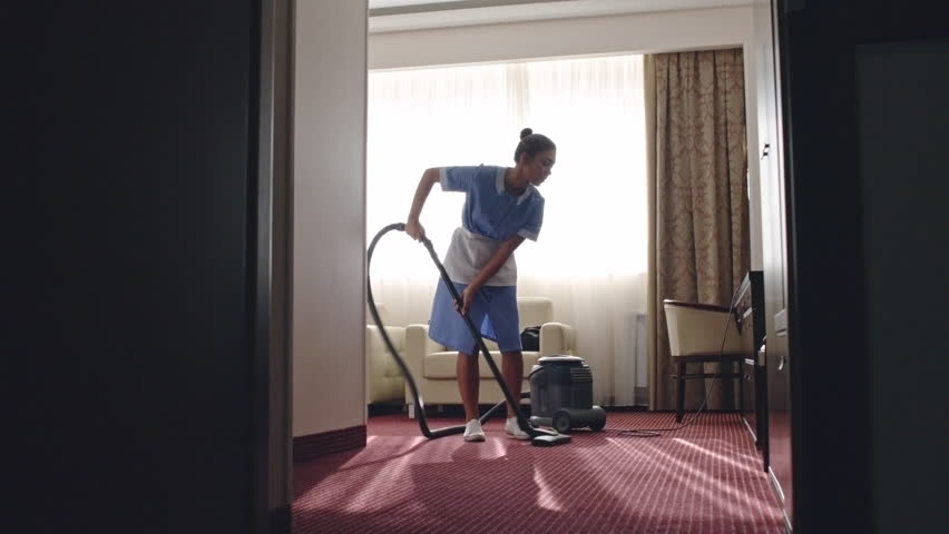 PAN of Latin American housemaid cleaning carpet in room with vacuum
