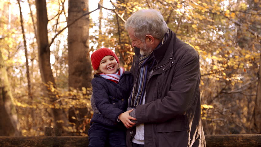 Granddaughter On Autumn Walk With Grandfather Sits On Fence