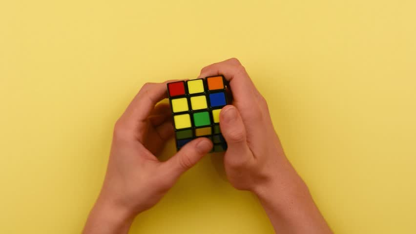 RYBNIK, POLAND -DECEMBER 24, 2016: Teenager's hands solving Rubik's cube puzzle.