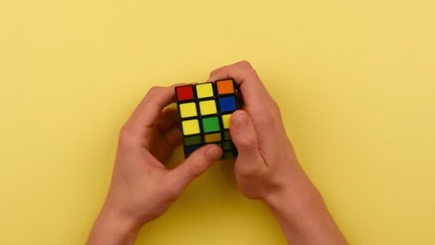 RYBNIK, POLAND -DECEMBER 24, 2016: Teenager's hands solving Rubik's cube puzzle.