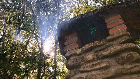 Smoke out of chimney flue in woods forest. Barbecue, bbq, barbeque, picnic chimney bricks. Smoke and sunlight through trees branches crowns foliage, leaves. Summer day. Smoke out of flue, funnel hole