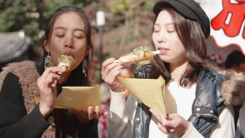 International girls enjoy street food in Kyoto Temple Japan while sightseeing. International and Japanese friends together in Kyoto Trip | Shutterstock HD Video #22573033