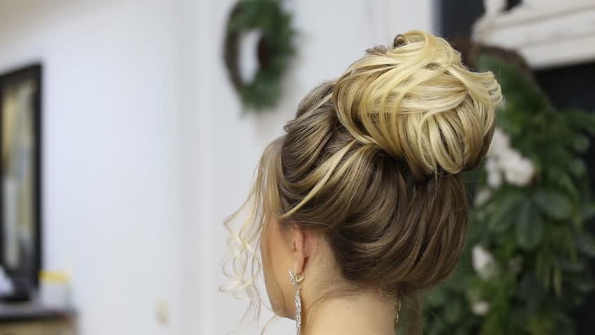 Hair stylist adds final touches to up do bun hairstyle of blonde woman in barber beauty salon