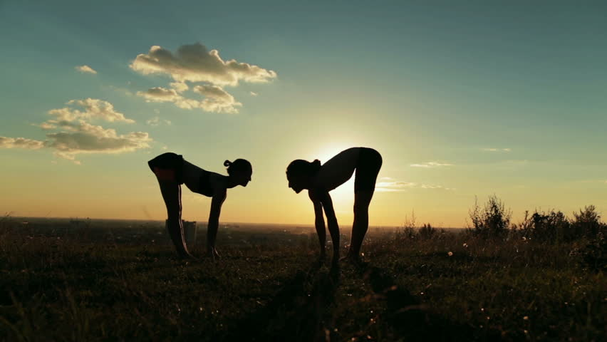 Silhouette of sporty man and woman doing Ashtanga yoga in the park at sunset. Sunset light, sun lens flares, golden hour. Freedom, health and yoga concept | Shutterstock HD Video #22585843