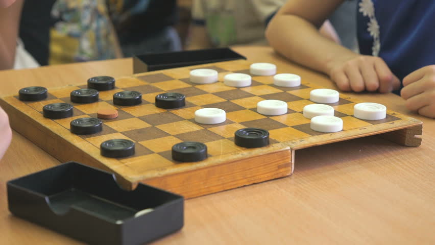 Children sit at the table and play checkers at the kindergarten. Close-up | Shutterstock HD Video #22595383
