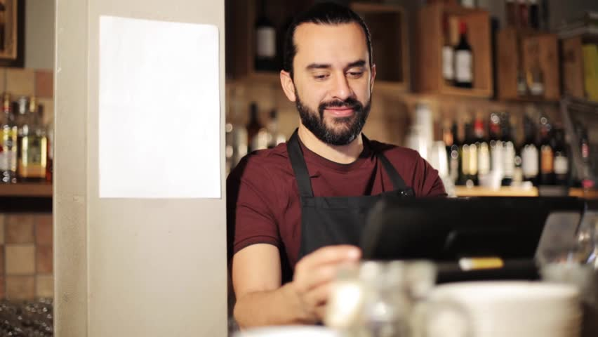 small business, people and service concept - happy man or waiter in apron at counter with cashbox working in coffee shop