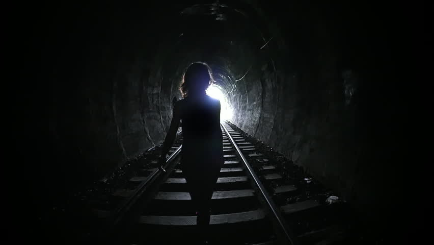 Mysterious woman walking in dark tunnel. Female silhouette on background of light at end of corridor. Person go alone in darkness. Death and afterlife concept. Urban subway with long tunnel