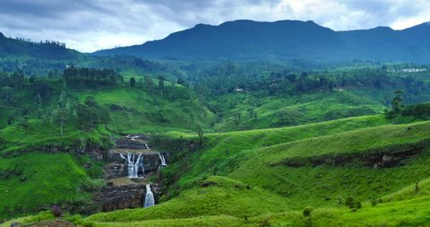 St. Clairs flowing down waterfalls in green huge humpbacked field with trees, green grass and mountains on background. Scene of calm wildlife in Sri Lanka without people and animals. Asian landscape