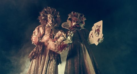 Actors Venetian carnival costumes on stilts with playing cards.