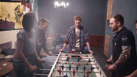 Novosibirsk, Russia DECEMBER 6, 2015: Group of young people playing table soccer in the bar