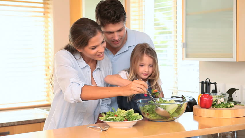 Family in the kitchen making a salad together and tossing it | Shutterstock HD Video #2271812