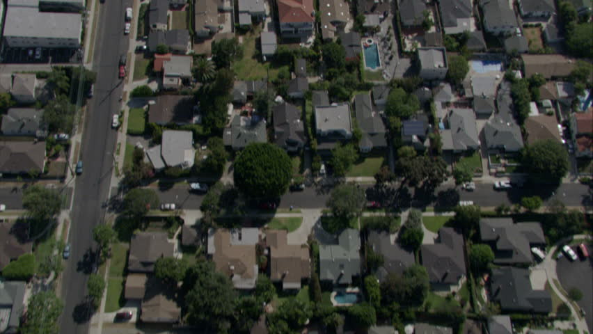 Fly over of homes in a residential area in Southern California separated by a freeway