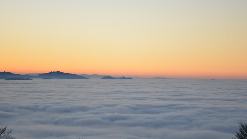 Clouds moving above the clouds on sunset from Pfänder. Time lapse view on Alps Mountains