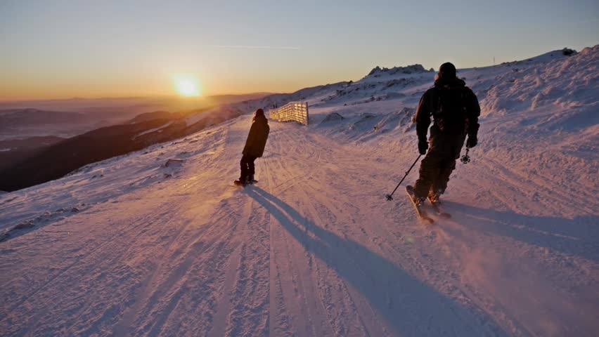 Slowmotion footage of a skier and snowboarder riding the slope during a beautiful sunset.