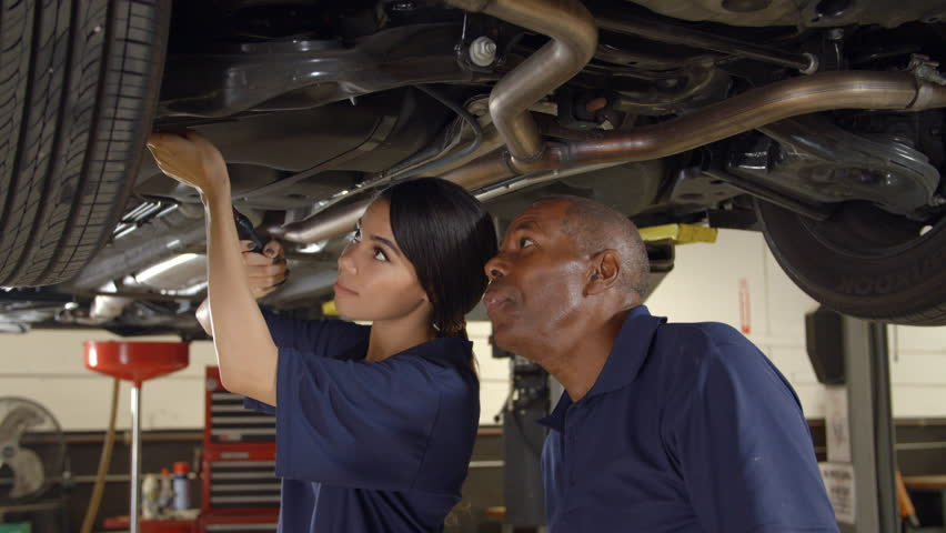 Mechanic And Female Trainee Working Underneath Car Together | Shutterstock HD Video #22758025