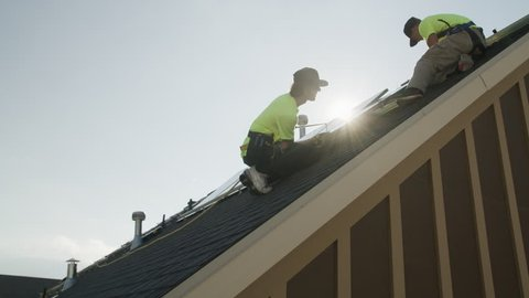 Medium panning low angle shot of workers installing solar panel on roof / Mapleton, Utah, United States