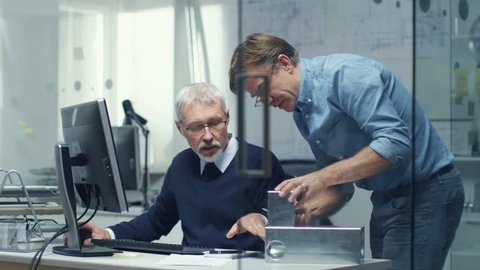 Two Senior Engineers Discuss Important Technical Component. Both are Experienced and Wise. Their Office Looks Modern and Bright. Shot on RED Cinema Camera in 4K (UHD).