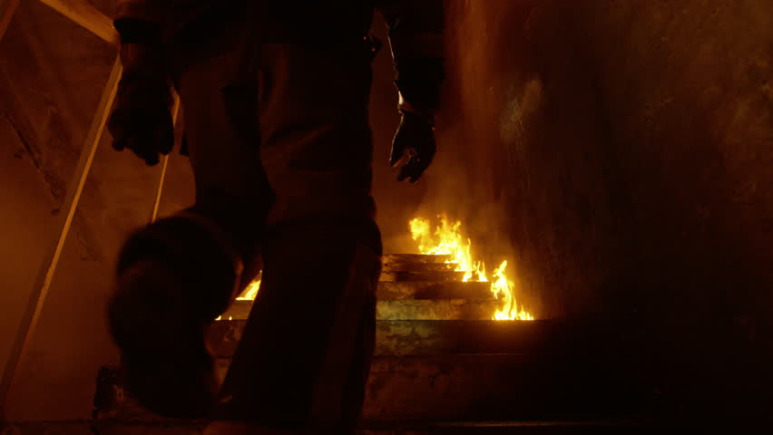 Brave Fireman Runs Up the Burning Stairs. Fire is Everywhere. In Slow Motion. Shot on RED Cinema Camera in 4K (UHD).