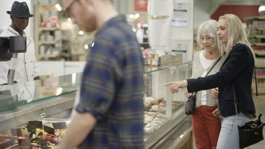 4K Senior lady & adult granddaughter shopping at deli counter in supermarket Dec 2016-UK | Shutterstock HD Video #22857913