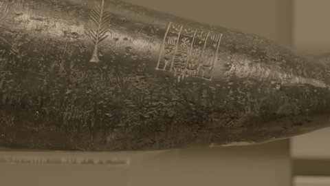 Manama, Bahrain - circa 2013 - CU tilt-up on a piece of black basalt carved with a feather and cuneiform writing from the Sumerian collection at the Bahrain National Museum.