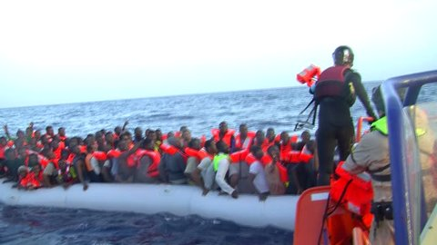 MEDITERRANEAN SEA, SEA/LYBIA-ITALY – OCT 25: Norwegian police of FRONTEX agency, rescues a rubber boat on 2016 mediterranean sea.