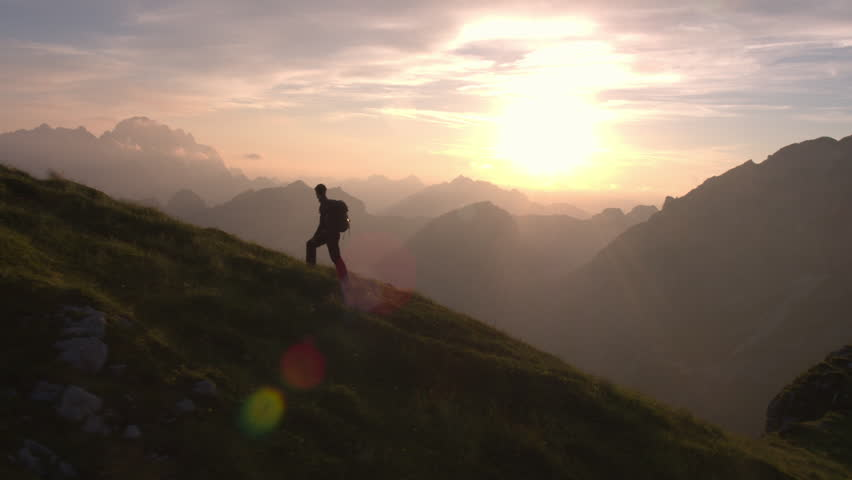 Aerial - Epic shot of a man hiking on the edge of the mountain as a silhouette in beautiful sunset #22952863