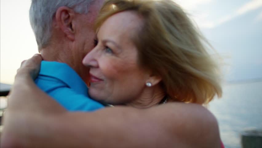 Loving seniors mature Caucasian couple leisure relax togetherness tourism healthcare dance beach resort sunset RED DRAGON   Shutterstock HD Video #22957903