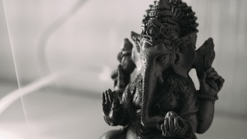 Lord Ganesha and Hinduism. Deity Ganesha with incense. Ganesha as a symbol of Hinduism, the God of wisdom and prosperity. Black & white color