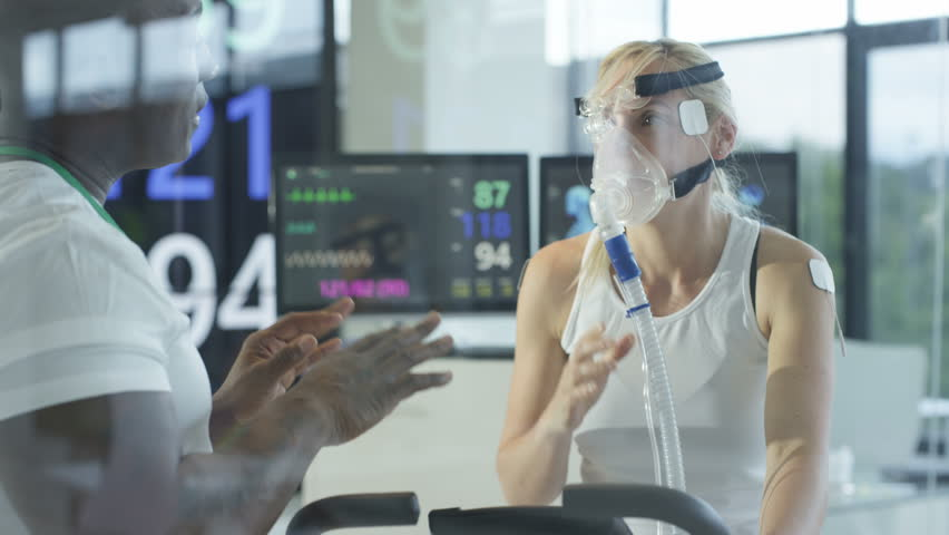 4K Female athlete on exercise bike being tested & monitored by sports scientist Dec 2016-UK | Shutterstock HD Video #22984693